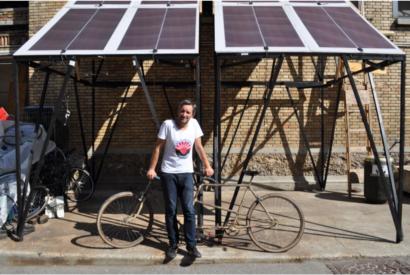 Cédric Carles devant un vélo sous un abri à panneau solaire